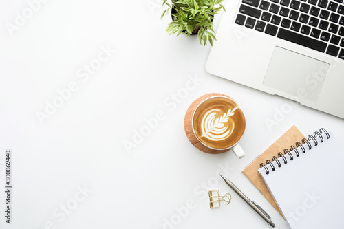 Obraz White minimalist office desk table with laptoo computer, notebooks with pen, cup of latte coffee and supplies. Top view with copy space, flat lay. - fototapety do salonu