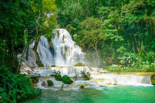 Kuang Si Falls Near To Popular Travel Destination Luang Prabang In Laos. Three Level Waterfall With Turquoise Blue Pools Surrounded With Lush Green Tropical Jungle.
