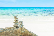 Stack Tower Of Stone Balances On A Beach With Water Sea And Blue Sky Nature