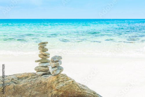 Foto auf Acrylglas Zen-Steine in den Sand stack tower of stone balances on a beach with water sea and blue sky nature