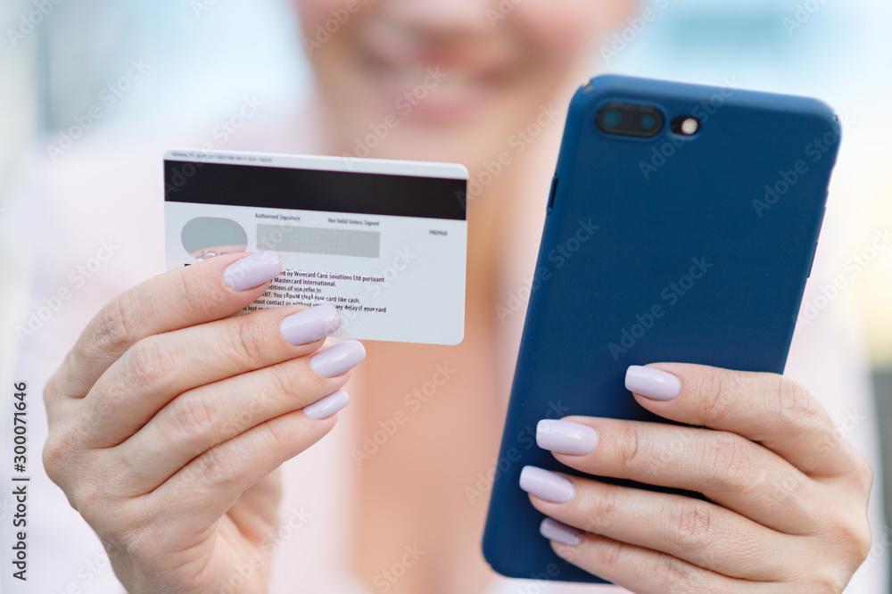 Fototapeta Businesswoman with a credit card and phone makes purchasing outdoors. Successful  woman is using smart phone and bank card for online shopping. Beautiful smiling white woman holds card and cell phone