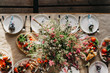 Table decoration with flowers and plates in a rustic style. With food