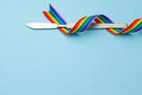 Fototapeta Tęcza - Scalpel and rainbow LGBT ribbon pride symbol. Sex change operation. Blue background. Copy space for text.