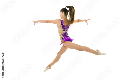 The girl gymnast performs a jump.