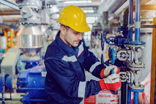 Obraz Dedicated hardworking worker in protective working clothes and with helmet on head screwing valve while standing in factory. - fototapety do salonu