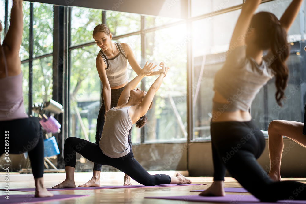 Fototapety, obrazy: Group of multi ethnics people learning Yoga class in fitness club. Female Caucasian instructor coaching and adjust correct pose to Asian girl student at front while others doing follow them.