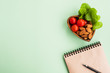 Concept of healthy eating, diet and new resolutions. Notebook and heart shaped plate with vegetables and nuts on a light green background. Top view, flat lay, copy space