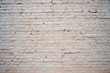 White painted brick wall with beige shade of color and volumetric shadows. Textured background