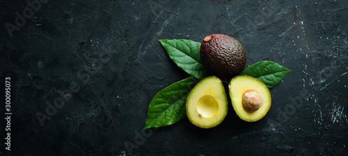 Fotografía Fresh avocado with leaves on a black background