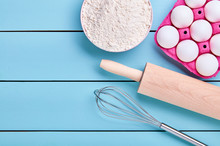 Ingredients For Baking, Eggs, Flour, Whisk And Rolling Pin On Blue Wooden Background