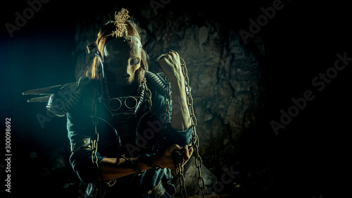 Post-apocalyptic woman in the rusty skull mask on the dungeon background Fototapete