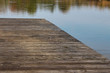 Old wooden boardwalk or pier on a lake with reflecting trees in the water