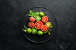 Fresh colored tomatoes in a black plate. Vegetables. On a black stone background. Top view.