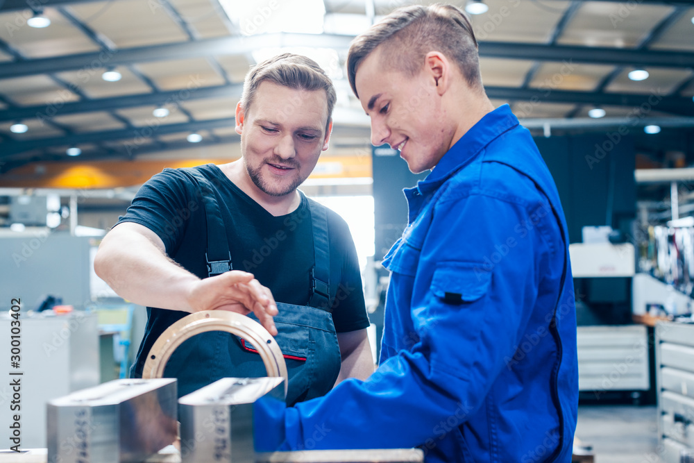 Fototapety, obrazy: Master discussing a workpiece with his apprentice or trainee