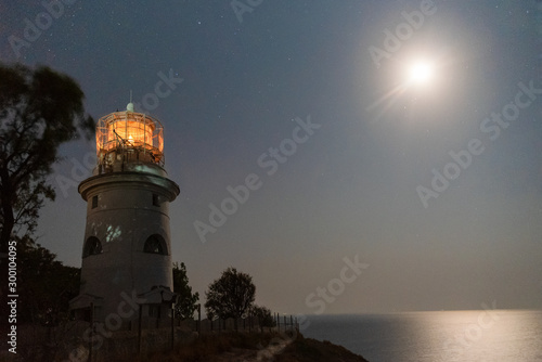 Autocollant pour porte Phare sea lighthouse on the shore at night with a bright moon in the night sky
