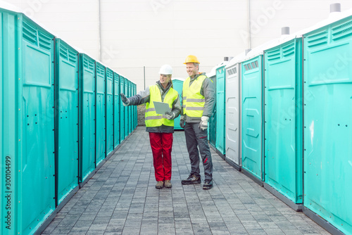 Obraz Workers checking the portable toilets for rental - fototapety do salonu