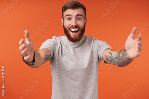 Valokuva  Happy attractive bearded man with tattooes being glad to see someone and would l