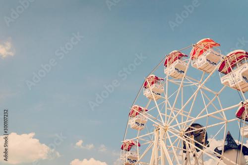 Fototapeta Ferris wheel on cloudy sky background with vintage toned. obraz