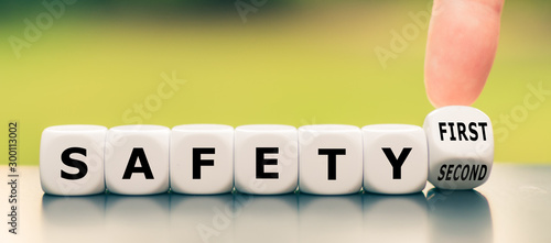 Leinwand Poster Hand turns a dice and changes the expression safety second to safety first