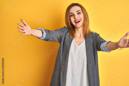 Fotografía  Redhead caucasian business woman over yellow isolated background looking at the camera smiling with open arms for hug