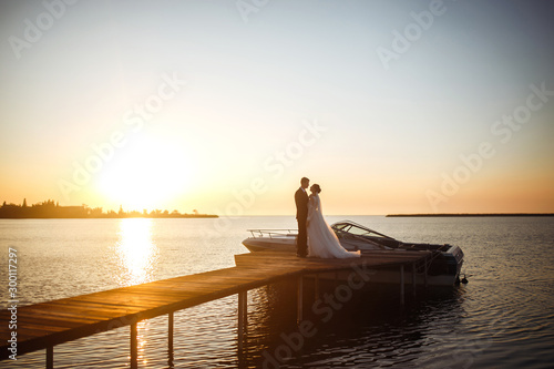 Beautiful bride and stylish groom together on the bridge against the background of the boat at sunset. Newlyweds tenderly hug, kiss and enjoy each other at sunset. Wedding. Love. Romantic moment.