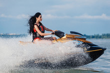 Athletic Brunette Rides A Jet Ski At Sea