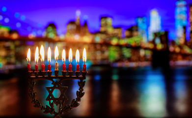 Hanukkah menorah symbol of Jewish traditional holiday Brooklyn Bridge over night New York City with lights