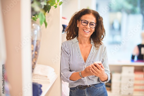Middle age beautiful businesswoman smiling happy and confident leaning on the wall using smartphone at clothes shop