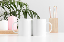 Two Mugs Mockup With Workspace Accessories And Candles On A White Table And A Palm Plant.