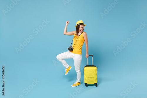 Ταπετσαρία τοιχογραφία Traveler tourist woman in yellow casual clothes, hat with suitcase photo camera isolated on blue background
