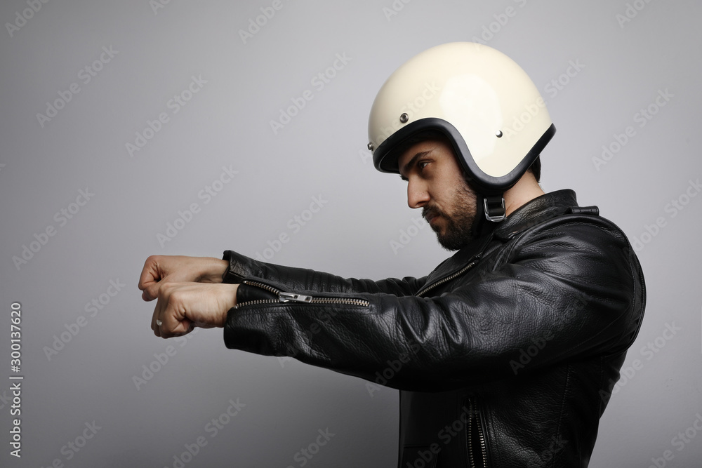 Fototapeta Young biker man in a leather jacket pretending to ride a motorcycle isolated on a white background. Horizontal.