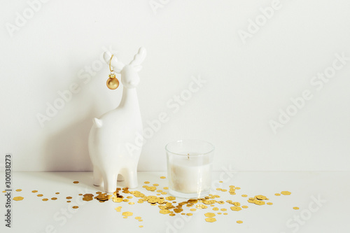 Christmas composition with White deer, candle and gold sparkles. Front view. Minimalist interior decoration