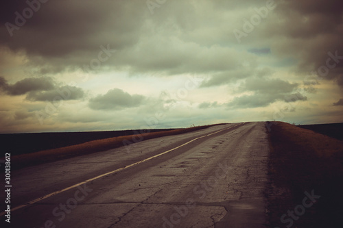 Asphalt road goes into the horizon and heavy autumn gray sky in cloudy autumn weather