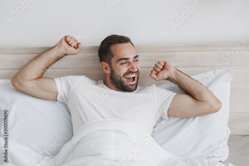 Obraz Calm young handsome bearded man lying in bed with white sheet pillow blanket in bedroom at home. Smiling beauty male spending time in room. Rest relax good mood lifestyle concept. Mock up copy space. - fototapety do salonu
