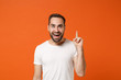 Leinwandbild Motiv Cheerful young man in casual white t-shirt posing isolated on bright orange wall background, studio portrait. People lifestyle concept. Mock up copy space. Holding index finger up with great new idea.