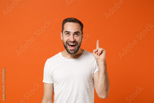 Fotografía  Cheerful young man in casual white t-shirt posing isolated on bright orange wall background, studio portrait