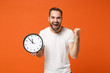 Leinwandbild Motiv Happy young man in casual white t-shirt posing isolated on bright orange background studio portrait. People sincere emotions lifestyle concept. Mock up copy space. Holding clock, doing winner gesture.
