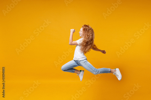 Fotografía  Side view of little ginger kid girl 12-13 years old in white t-shirt isolated on yellow background children portrait