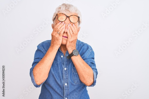 Valokuva  Senior grey-haired woman wearing denim shirt and glasses over isolated white background rubbing eyes for fatigue and headache, sleepy and tired expression