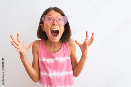 Young beautiful child girl wearing pink t-shirt and sunglasses over isolated white background crazy and mad shouting and yelling with aggressive expression and arms raised Fototapete