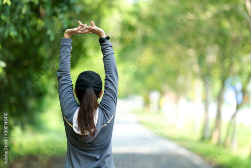 Fototapeta Healthy woman warming up stretching her arms. Asian runner woman workout before fitness and jogging session on the road nature park. Healthy and Lifestyle Concept obraz