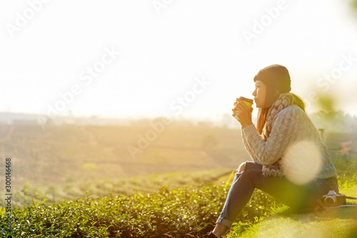 Carta da parati Asian lifestyle women wearing sweater, sitting and drinking hot coffee or tea relax outdoor in the sunrise morning sunny day at tea plantation nature