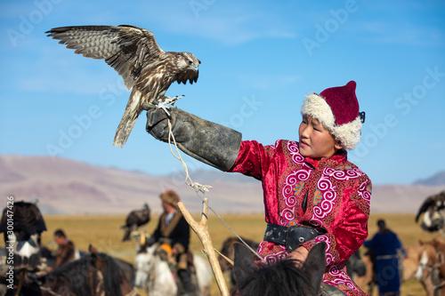 Young Mongolian boy in traditional Mongolian dress holding his falcon on horseback Wallpaper Mural