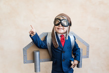 Portrait Of Young Businessman With Toy Paper Wings