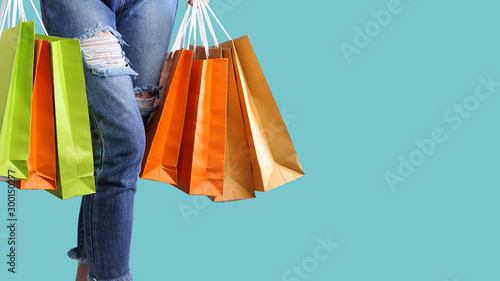 Fototapeta  Shopping bags on women hands on the pastel isolated background