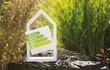 canvas print picture - Weißes Haus im Garten mit Schild Energielabel