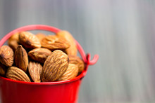 Close Up On Group Of Almond Seed Containing In Red Bucket For Eating Healthy Lifestyle Concept