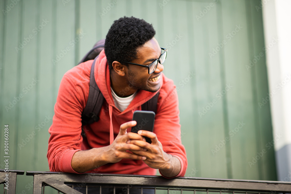 Fototapeta young african american man with glasses and mobile phone looking away