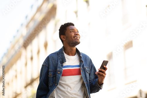 Fotografiet  happy african american man holding cellphone in city