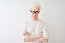 Young Albino Blond Man Wearing T-shirt And Glasses Standing Over Isolated White Background Skeptic And Nervous, Disapproving Expression On Face With Crossed Arms. Negative Person.